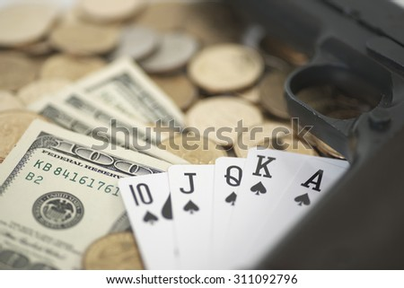 Abstract shallow DOF of royal flush card and gun over pile of dollar money - stock photo