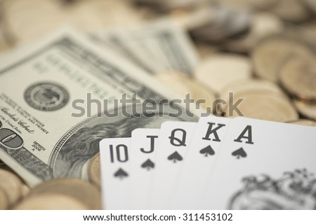 Abstract shallow DOF of royal flush card over pile of dollar money - stock photo