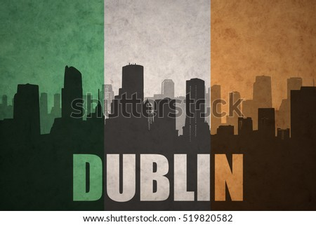 abstract silhouette of the city with text Dublin at the vintage irish flag background