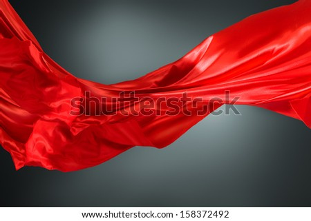 Abstract silk red cloth motion against dark background - stock photo