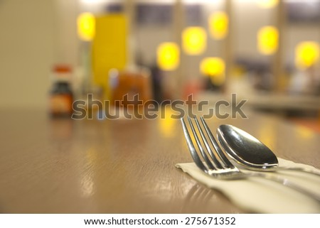 Abstract silverware on top of table with blurry restaurant background - stock photo