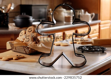 Abstract still life of oversized gingerbread man cookie cutter on marble countertop with baking supplies.  Extremely shallow dof with selective focus limited to the cookie cutter. - stock photo