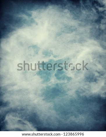 Abstract storm clouds on a textured paper background.  Image has a distinct grain pattern visible at 100%. - stock photo