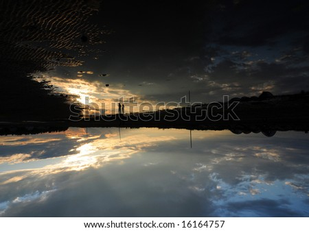 Abstract Sunset in Nova Scotia. The image has been flipped to highlight the people reflected in the tidal pool. - stock photo