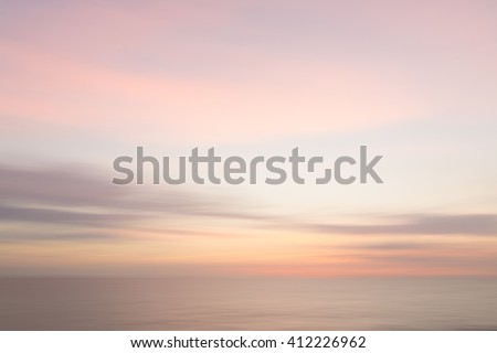 Abstract sunset sky and ocean nature background with blurred panning motion. - stock photo