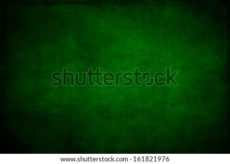 Abstract textured green or Christmas  background with bright center spotlight and black vignette border. With a vintage grunge background texture. - stock photo