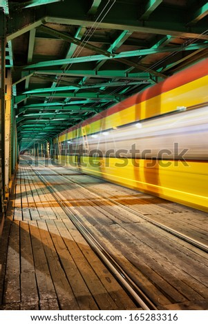 Abstract tram light trail in the lower part of the steel truss Gdanski Bridge in Warsaw, Poland, vanishing point perspective. - stock photo