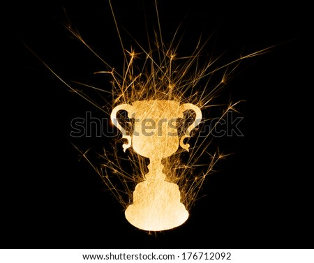 Abstract trophy in bright sparks with copy space on black background. - stock photo