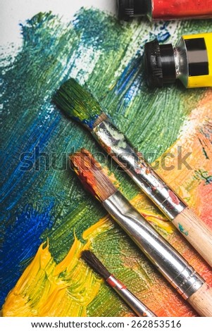 Abstract. Two paintbrushes are painting a rainbow splattered art project. The brushstrokes are messy on a white isolated background.  - stock photo