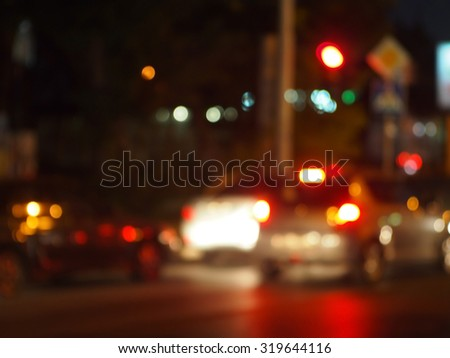 Abstract urban night scene with blurred headlights on the road. Blur and defocused lights on the flow of cars and traffic lights can be used as background. - stock photo
