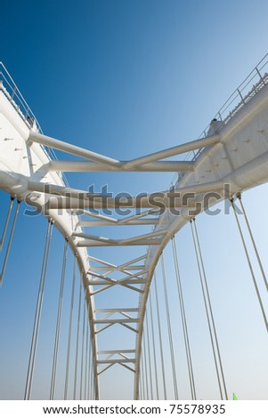 Abstract view of bridge support against a blue sky. - stock photo