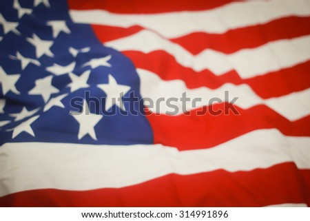 abstract vintage blurred crumpled retro american flag with vignette backgrounds:blur crumpled and creased fabric textures of American flag with vignette backgrounds.patriotic concept.veteran day. - stock photo