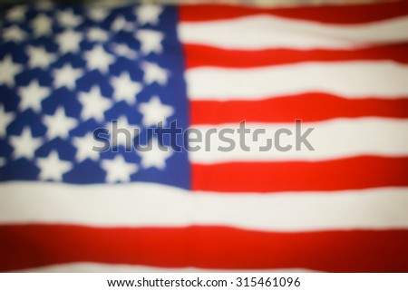 abstract vintage blurred crumpled retro american flag with vignette backgrounds:blur crumpled and creased fabric textures of American flag with vignette backgrounds.patriotic and veteran day concept. - stock photo