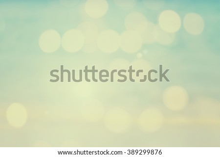 abstract vintage filter effect of blurred background:blur beach sunlight backdrop with motion circle light in soft pastel color warm tone.blurry bokeh glitter sparkle wallpaper:glowing bright display - stock photo