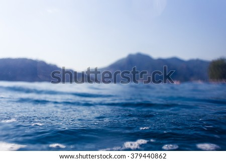 Abstract water line landscape with mountains background. Defocused with shallow depth of field. Abstract underwater background. Wave against the sky. Blue ocean landscape.  - stock photo
