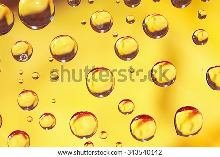 Abstract yellow background with various water drops - stock photo