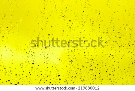 Abstract yellow drops of water on glass - stock photo