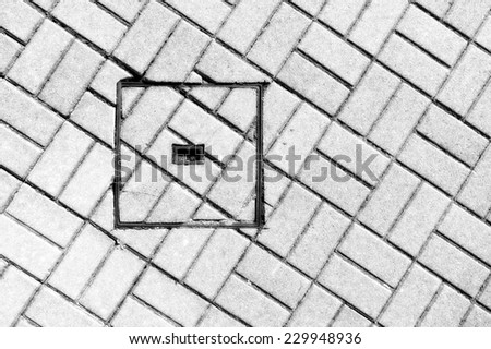 abstraction of steel sewer manhole on floor with cobblestone - stock photo