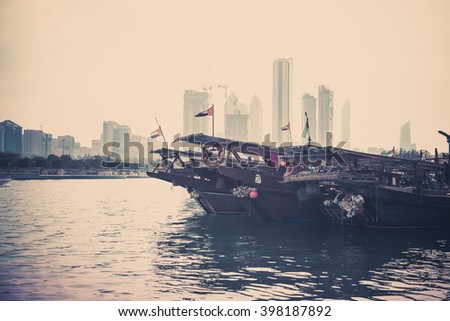 Abu Dhabi buildings skyline with old fishing boats on the front. Filtered shot