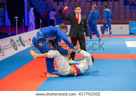 ABU DHABI, UAE - APRIL 19, 2016: ABU DHABI WORLD PROFESSIONAL JIU-JITSU CHAMPIONSHIP 2016 in the IPIC ARENA. Fighters fighting in arena. The referee gives a point