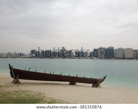 Abu Dhabi, United Arabic Emirates - March 21, 2015: ancient boats as exponents in Emirates Heritage Club and Heritage Village - view on downtown of Abu Dhabi. Emirates Heritage Village, Abu Dhabi.