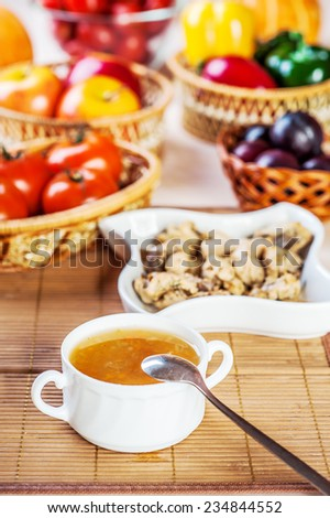 abundance food meat , vegetables, fruits (stewed chicken, tea, tomatoes, peppers, apples, plums) background wooden table - stock photo