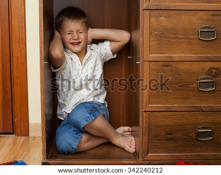abuse and cruelty to children - little boy is hiding in a cupboard in the room, closing his ears by hands - stock photo