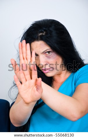 Abused scared woman  with bruises on face sitting  and showing stopping hands - stock photo