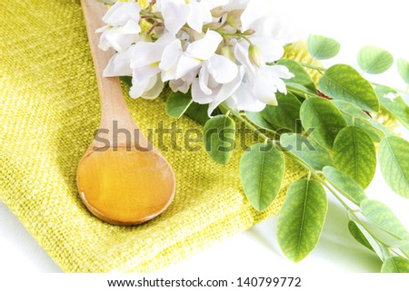 Acacia honey in spoon with flower and leaves
