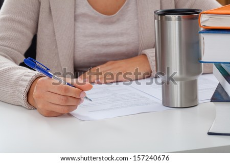 Academic teacher during writing an article with a coffee and books - stock photo