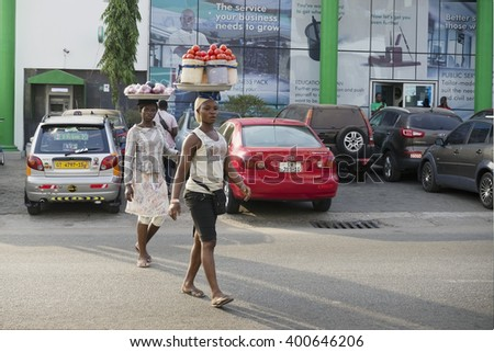 ACCARA, GHANA - JANUARY 22, 2016:  African women bear on head tomatoes and potatoes for sale in street market. One of the central streets of the capital of Ghana with banks and offices