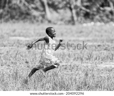 ACCARA, GHANA - MAR 2, 2012: Unidentified Ghanaian little girl runs heppily in the field in black and white. People of Ghana suffer of poverty due to the unstable economical situation