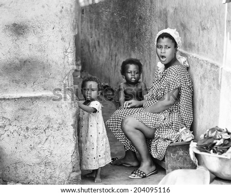 ACCARA, GHANA - MAR 2, 2012: Unidentified Ghanaian mother and her two little daughters in the street in black and white. Children of Ghana suffer of poverty due to the unstable economical situation