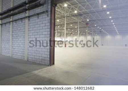 Access door to brightly lit and empty warehouse - stock photo