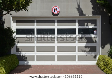 Access to a garage with a no parking sign displayed above the door - stock photo
