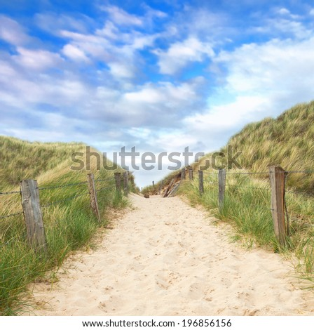 access to the beach, behind the dunes there is an impressive view of the sea - stock photo