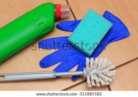 Accessories for cleaning bathroom on ceramics flooring, brush, glove, sponge, concept for house cleaning and household duties - stock photo