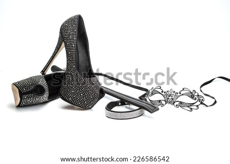 Accessories for fetish role playing: mask in venetian style, leather whip, collar with rhinestones and platform high heels with rhinestones;  - stock photo