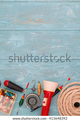 Accessories for fishing on the background of wood. Background of blue color. Reel, fishing line, float, net hooks, red flashlight, a coil of rope. Bait for fishing. - stock photo