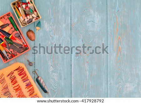Accessories for fishing on the background of wood. Background of blue color. Several float, hook, sinker. Bait for fishing. - stock photo