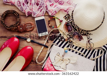 accessories for teenage girl on her vacation. Straw hat, stylish sunglasses, pink leather bag, red shoes and striped beach dress on wooden floor. - stock photo