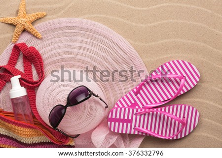 Accessories for the beach lying on the sand beach, with place for your text