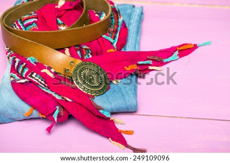 accessories on a lilac background  - scarf, belt,  jeans,  - stock photo