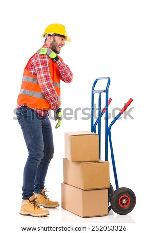 Accident at work. Manual worker holding shoulder in pain. Full length studio shot isolated on white. - stock photo