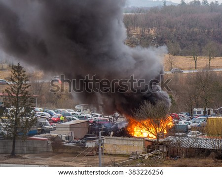 Accident dangerous car fire. Dark black grey smoke car service station. Danger flame extinguished firefighters. Car fire exploded. Car fire explosion, arson, arsonist. Lots, plenty cars fire burn - stock photo