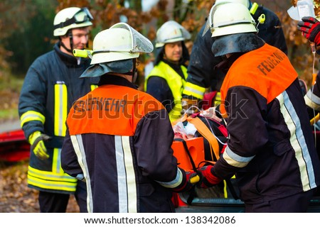 Accident - Fire brigade and Rescue team pulling cart with wounded person wearing a neck brace and respirator - stock photo