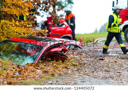 Accident - Fire brigade rescues accident Victim of a car, a car door lying on the slippery pavement - stock photo