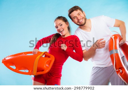 Accident prevention and water rescue. Young man and woman lifeguard couple on duty holding buoy lifesaver equipment having fun on blue - stock photo