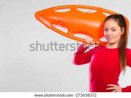 Accident prevention and water rescue. Young woman female lifeguard on duty holding float lifesaver equipment on gray. Copy space - stock photo