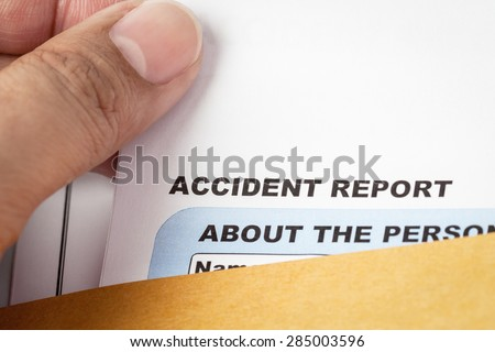 Accident report application form and pen on brown envelope and eyeglass, business insurance and risk concept; document is mock-up - stock photo